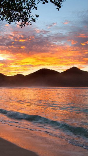 Sunset with mountains on beach